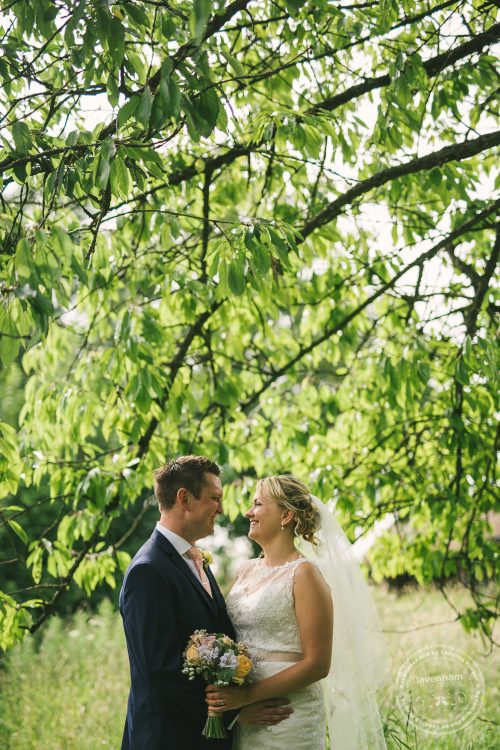 Bride and groom photographed in trees, by Lavenham Photographic