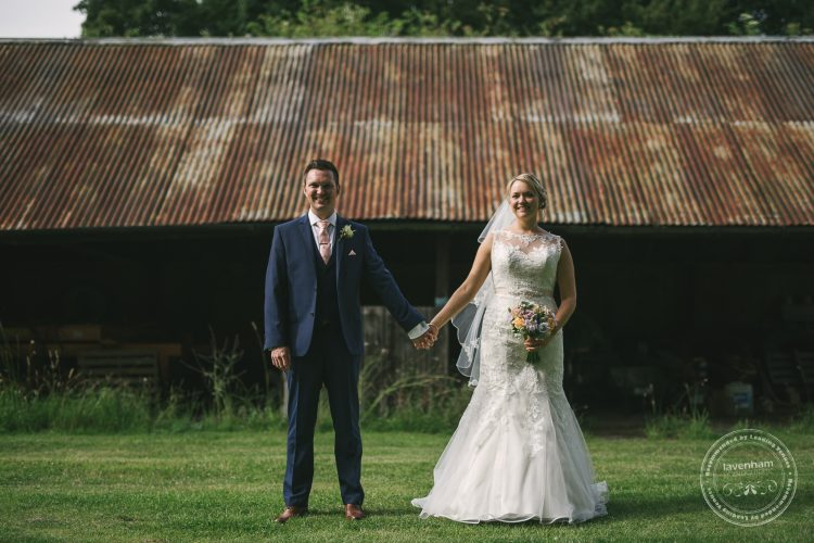 Wedding couple holding hands in front of rusty barn roof