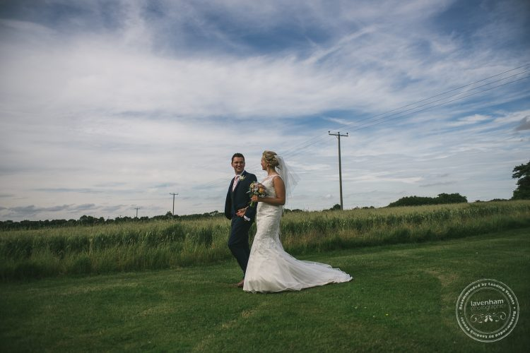 Wedding photography, bride and groom walking in front of field with big blue sky and whispy clouds