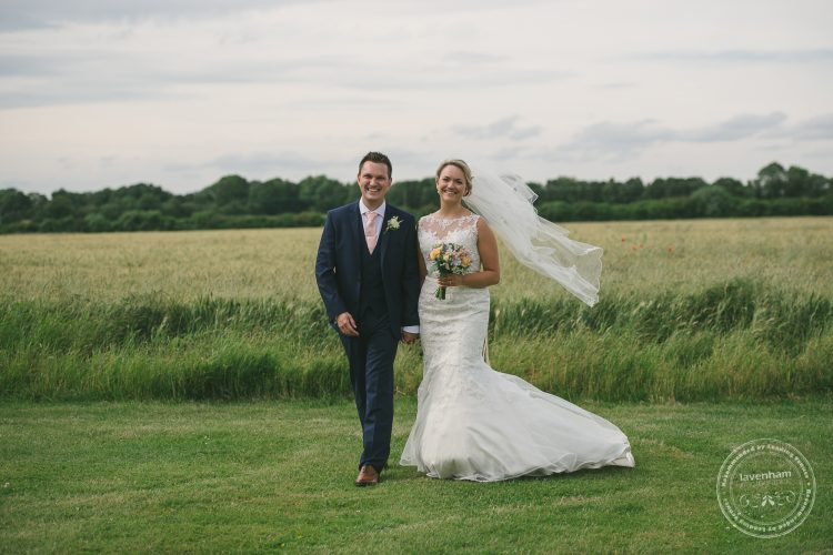 Wedding photography, bride and groom walking in front of field
