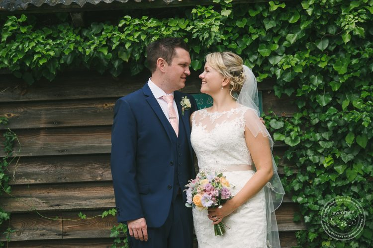Bride and groom photographed in front barn, Ivy and wood