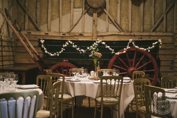 The dining room setup at Preston Priory Barn, with large horse-drawn carriage in background