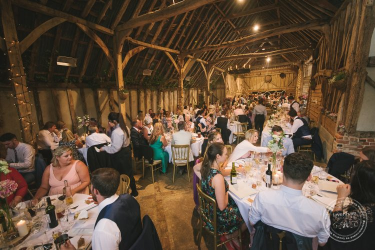The wedding guests enjoying their dinner inside Preston Priory barn