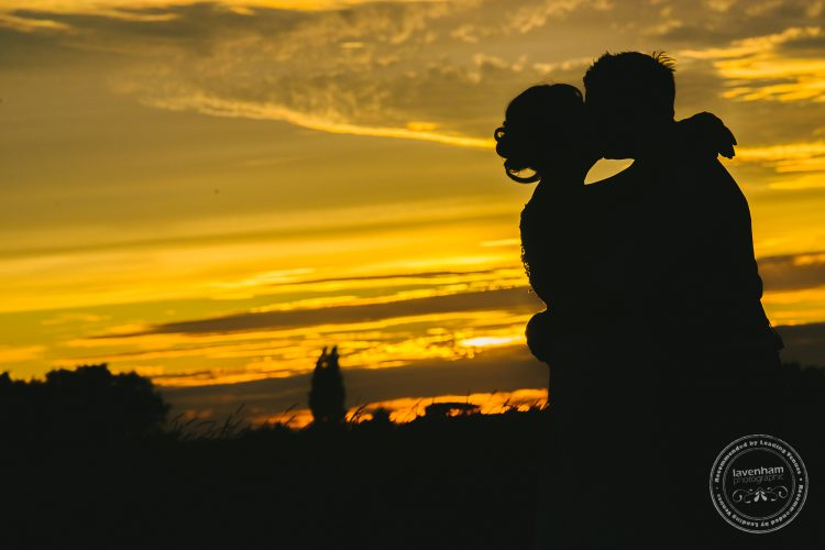 Bride and groom sillhouetted against sunset sky by Lavenham Photographic