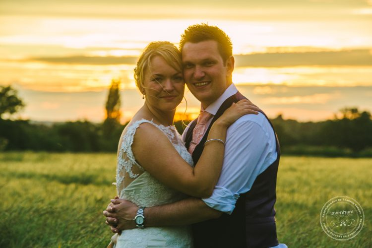 Bride and groom, sunset behind
