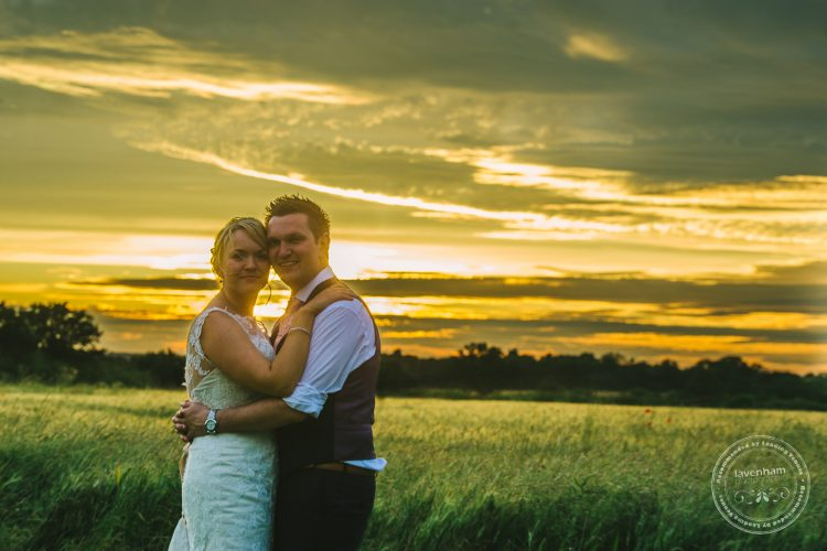 Bride and groom, field and sunset behind