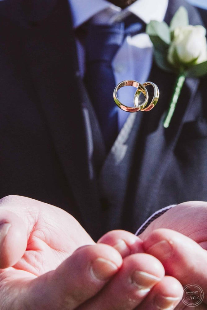 The wedding rings photographed in mid-air, dropping into the groom's hands