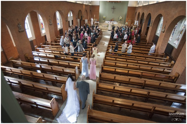 Church wedding ceremony, photographed from above as the bride walks down the aisle