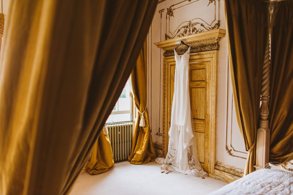 Brides wedding dress hanging in the Rococco Suite at Gosfield Hall