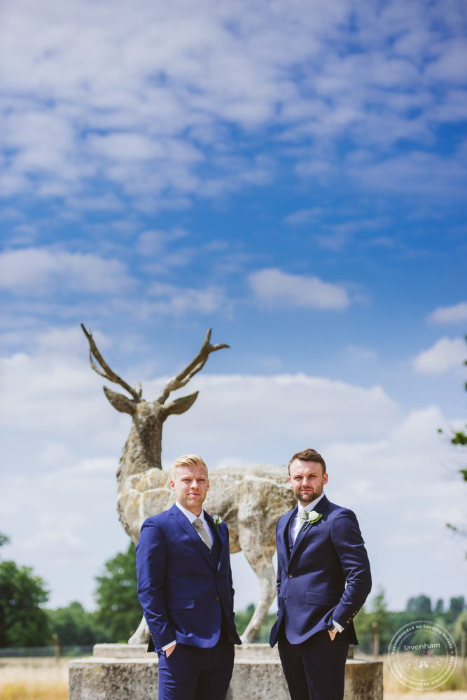 Photography of the groom with his best man with one of the stag statues at Gosfield Hall before the wedding ceremony