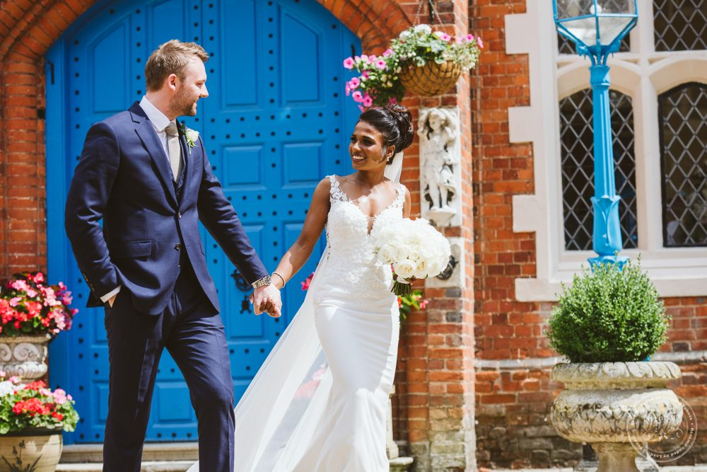 The bride and groom take a walk in the courtyard at Gosfield Hall