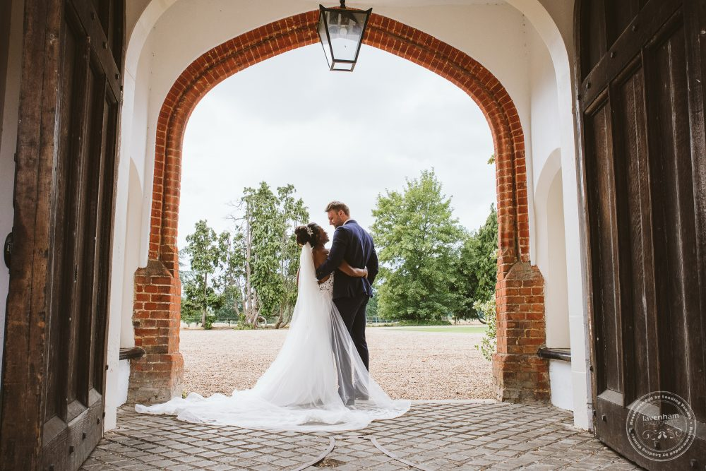 Wedding photography at Gosfield Hall, framed with an archway in the courtyard
