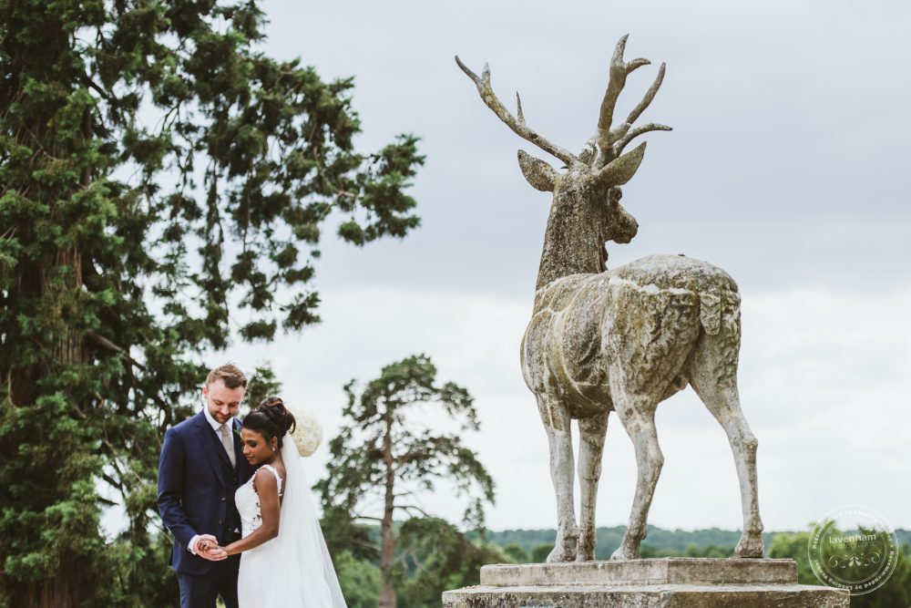 The bride and groom photographed with a stag statue in the grounds at Gosfield Hall