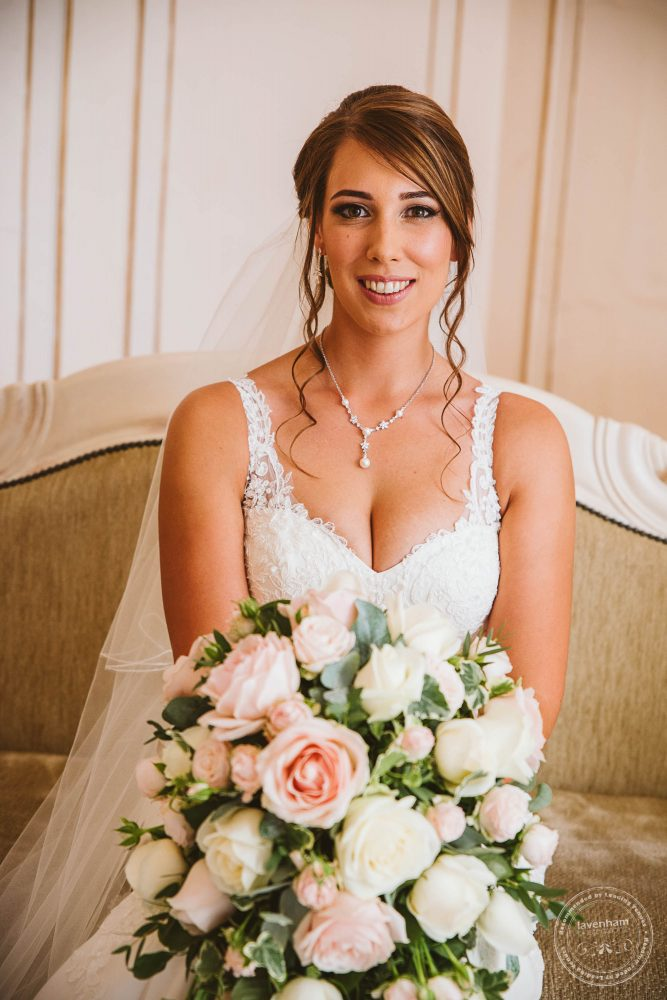 The bride sitting on the sofa in the Rococo suite before the Gosfield Hall wedding ceremony