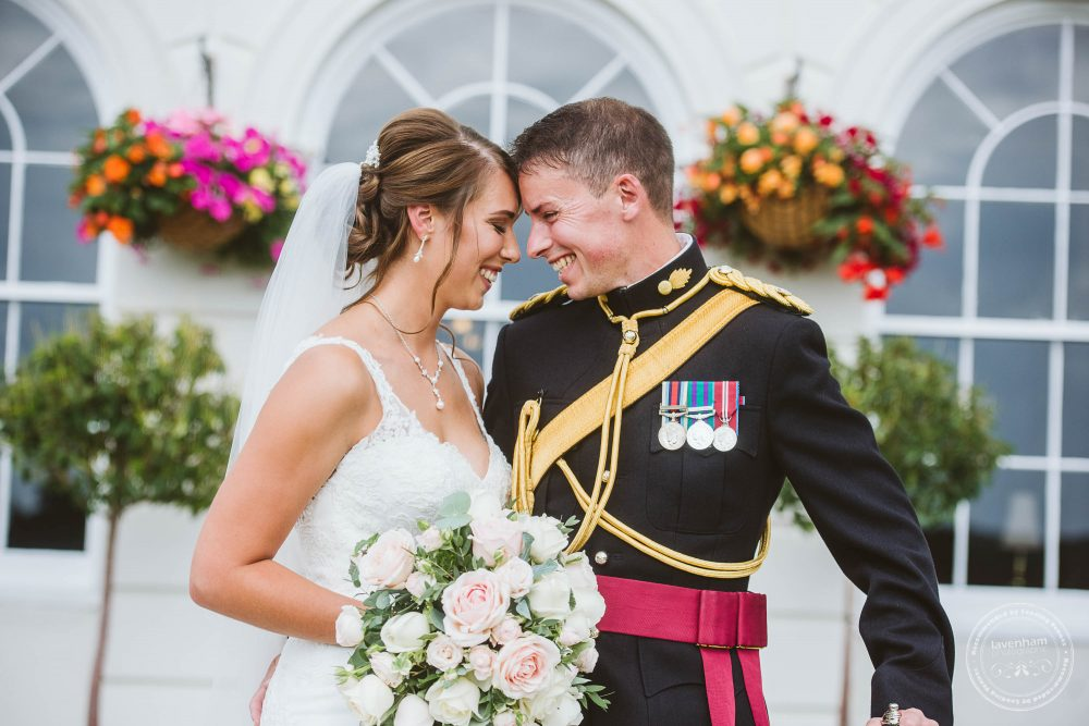 Bride and Groom in front of colourful hanging baskets at Gosfield Hall's white south face