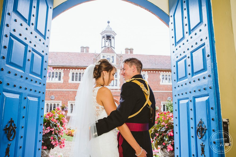 Bride and groom photographed in the doorway of Gosfield Hall's famous blue doors