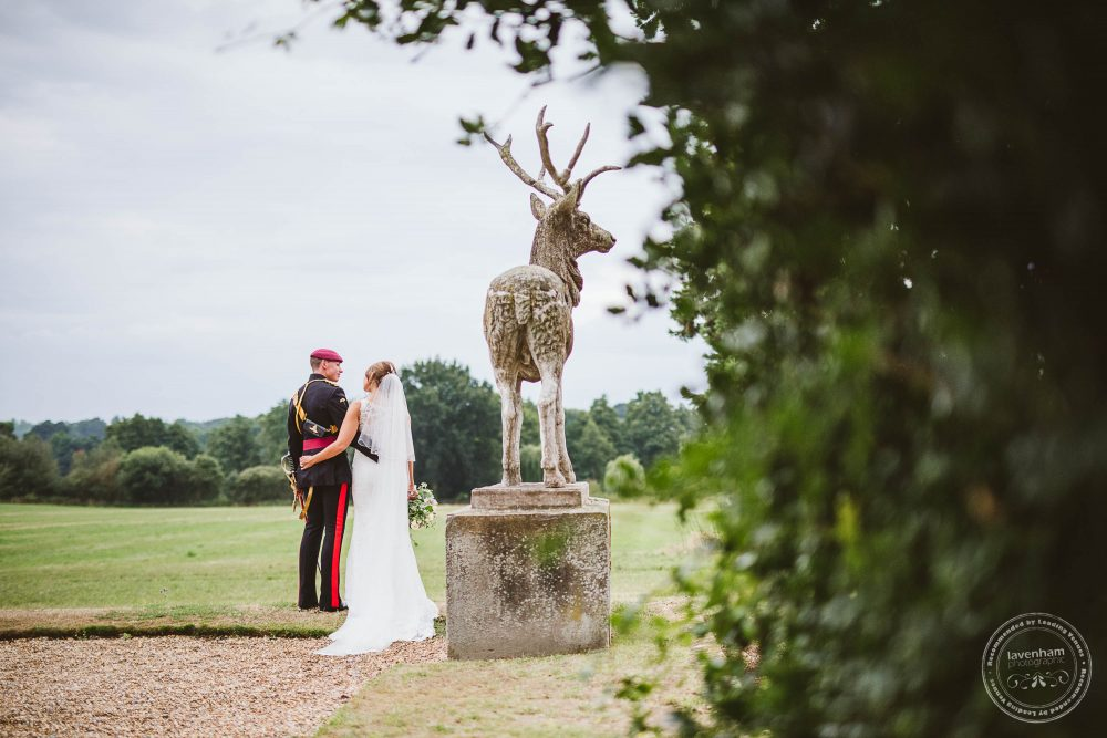 Bride and groom with the stag in the grounds at Gosfield Hall