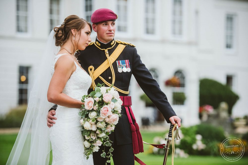 Bride in her wedding dress with bouquet with groom in military dress look into the distance at Gosfield Hall wedding