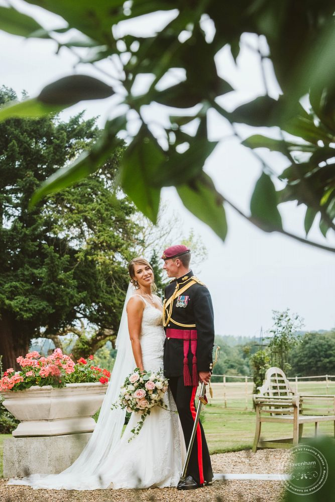 Photograph of the Bride and groom, framed with leafy foliage at the top of the frame