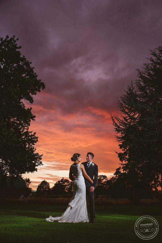 Photograph of the bride and groom with a sunset sky