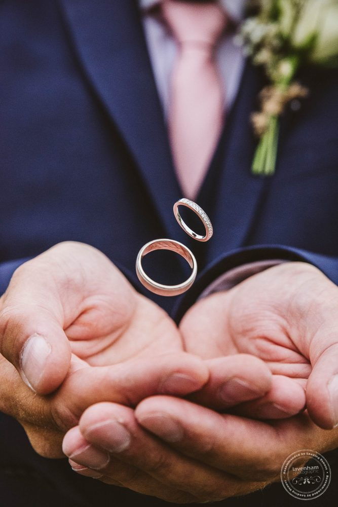 Detail photography of wedding rings dropping into the groom's hands