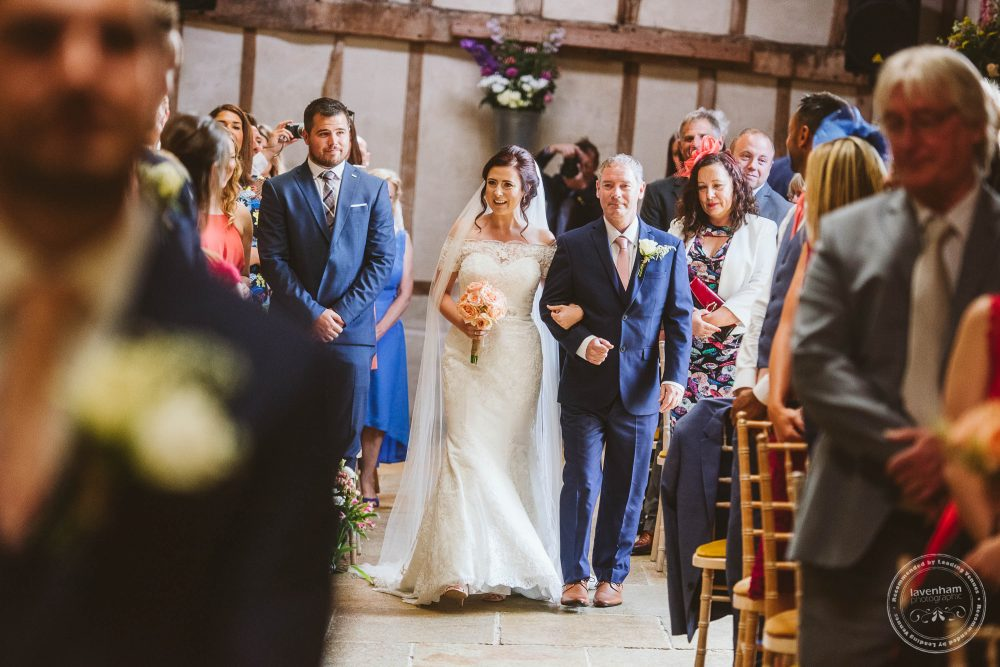 Bride walks down the aisle for the wedding ceremony at Alpheton Hall Barn