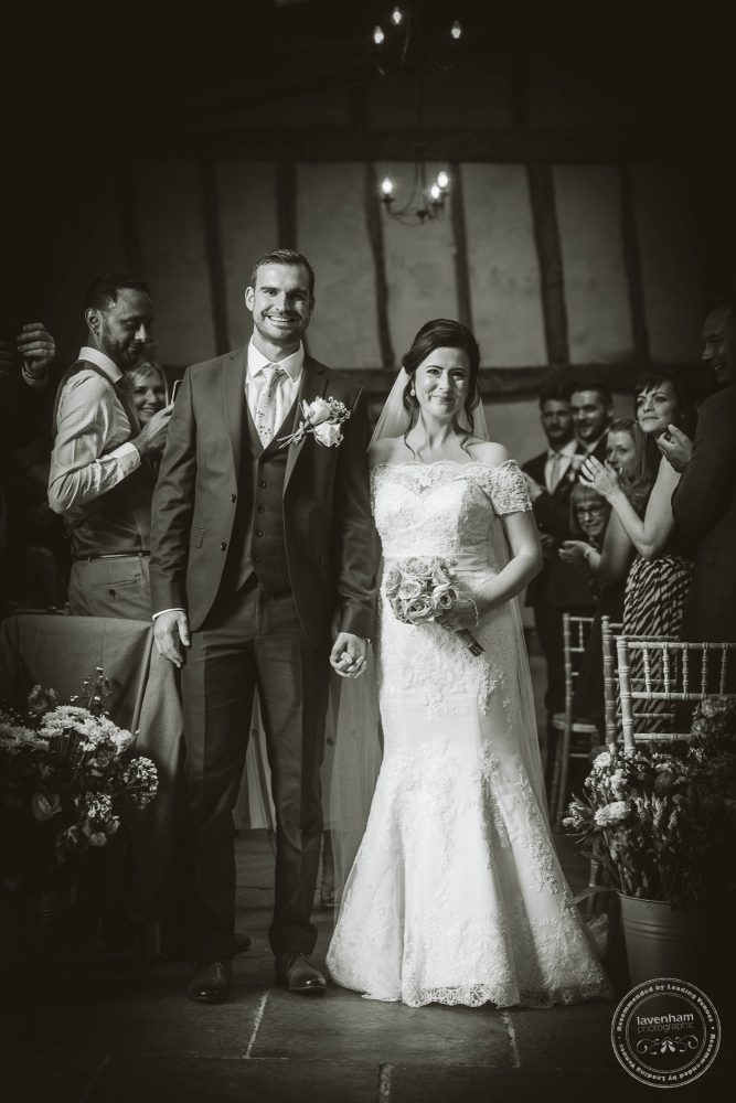 Black and White Photograph of the bride and groom walking down the aisle married at Alpheton Hall Barns Wedding
