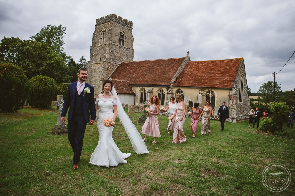 Lisa & Bryn lead their guests from the wedding ceremony to the reception in the garden at Alpheton Hall Barn