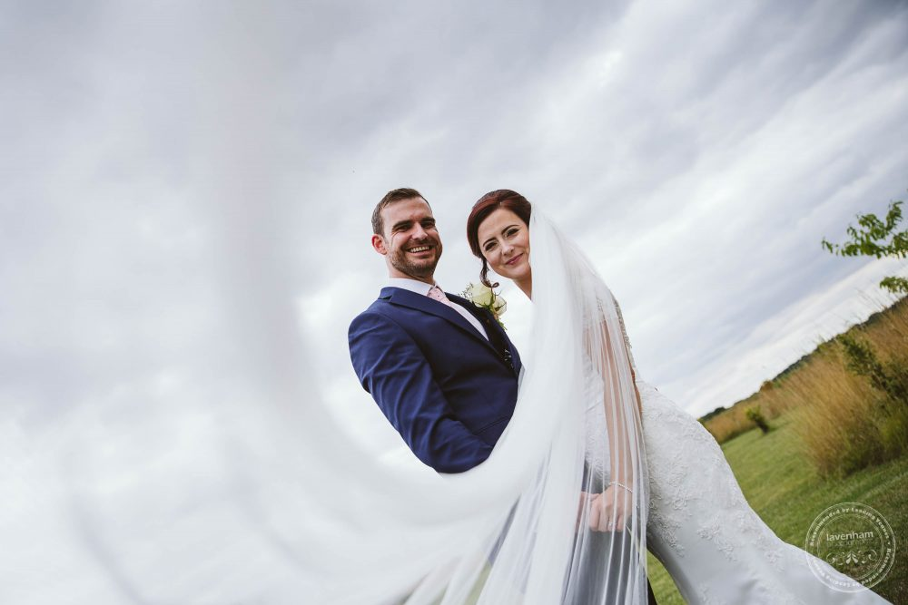 Bride and groom photographed with wedding veil flying dramatically through the photo