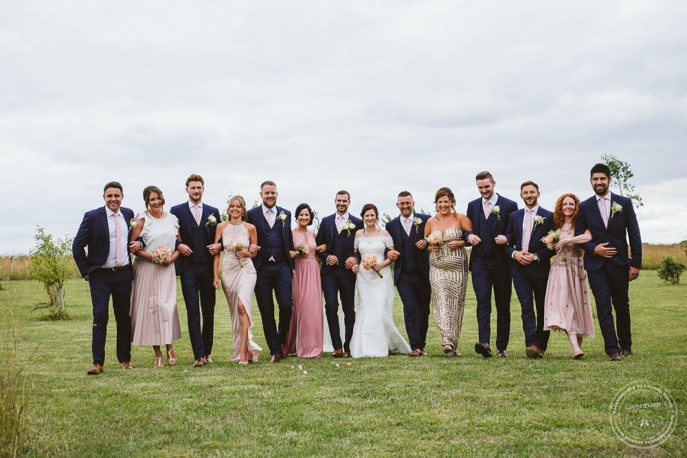 Wedding party walk in a large group photograph