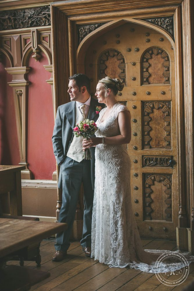 Bride and groom with a detailed old door at Kentwell Hall
