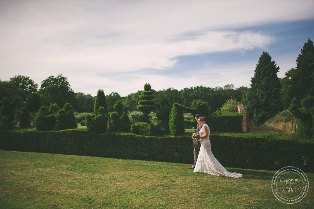 Bride and groom walk in the grounds at Kentwell, with amazing topiary in the hedges.