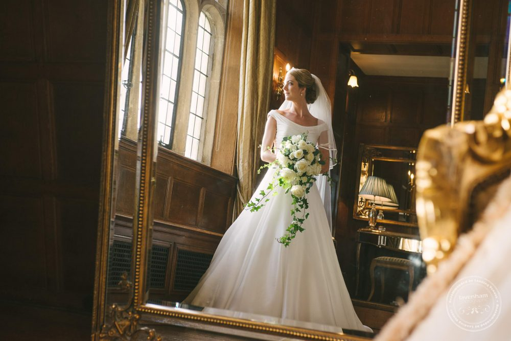 The bride photographed in a huge mirror in the bridal suite at Hengrave Hall