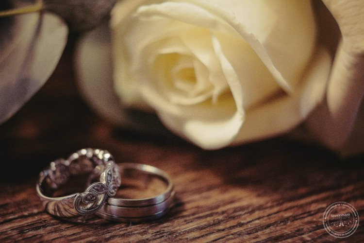 Detail of intricate wedding rings against wooden table