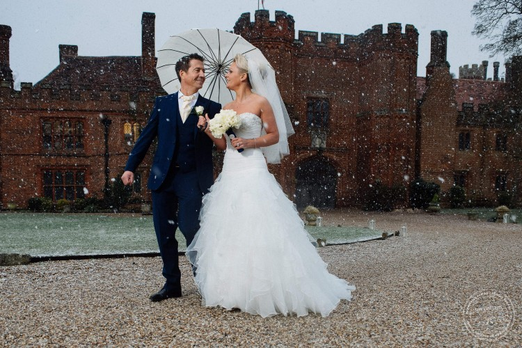 Bride and groom walk in the snow with umbrella. Leez Priory Wedding Photography by Lavenham Photographic