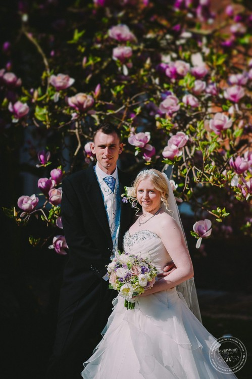 Bride & groom with pink blossom at Gosfield Hall, Essex