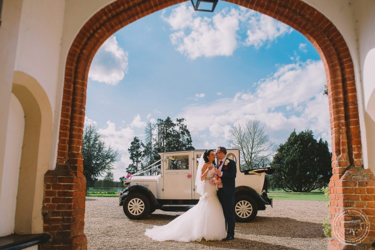 Bride & groom with wedding car and blue sky photographed through archway at Gosfield Hall, Essex