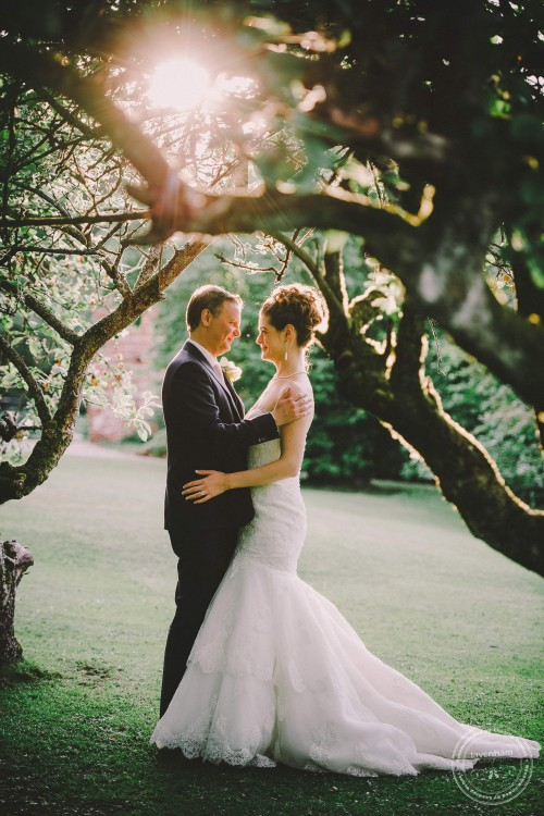 Wedding Photograph with evening light, shot through trees at Leez Priory, Essex