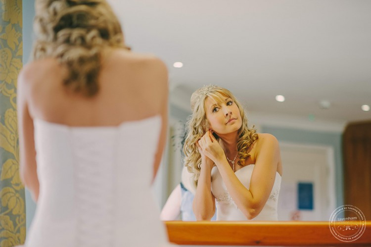 Bride putting on earrings in mirror. Wedding photography by Lavenham Photographic