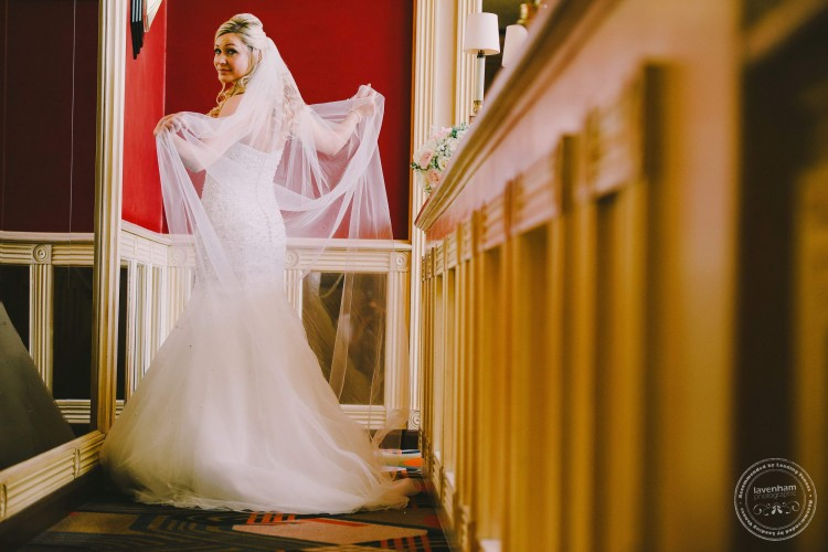 Bride holding veil. Wedding Photography by Lavenham Photographic