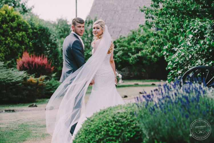 Bride and groom walking, veil blowing. Wedding Photography by Lavenham Photographic