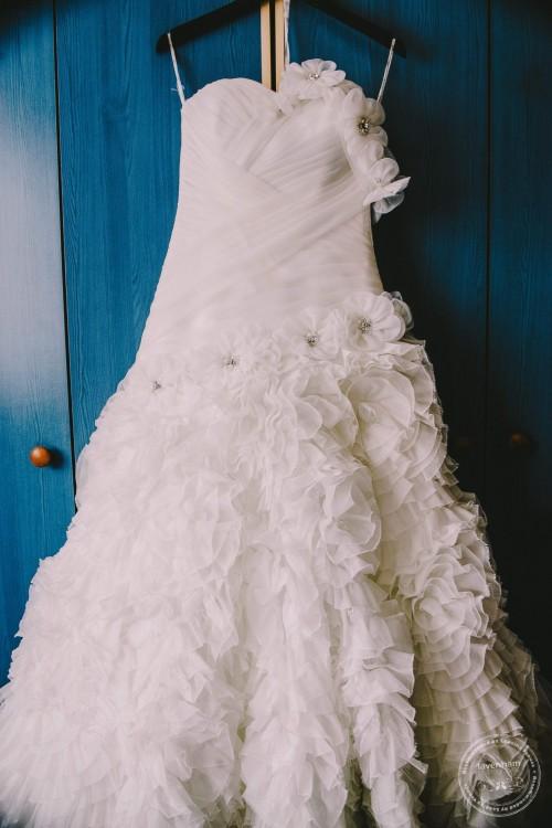 Wedding dress detail photographed hanging with blue door