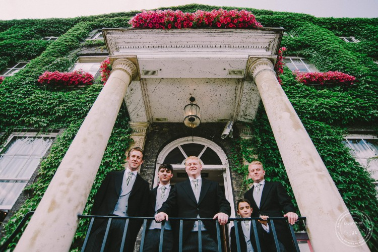 Groom with groomsmen with ivy and pink flowers on the balcony at the Angel Hotel in Bury St Edmunds