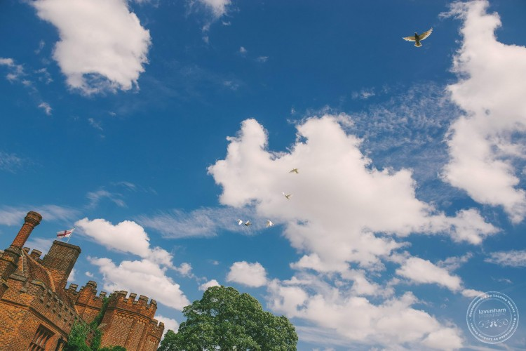 Doves flying over Leez Priory. Wedding Photography by Lavenham Photographic