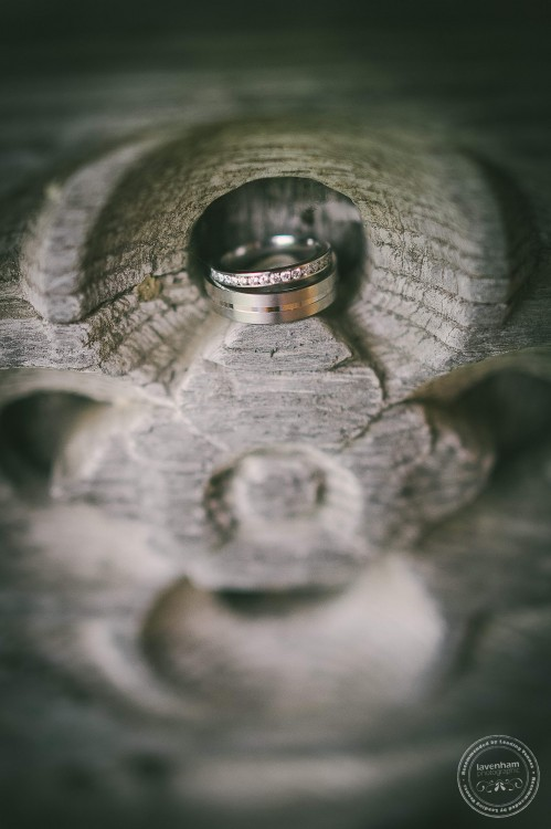 Wedding rings photographed in detail in wooden carving in old door at Leez Priory