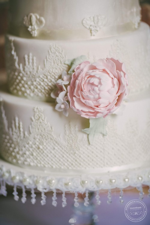 Wedding cake with lace detail and pink flower
