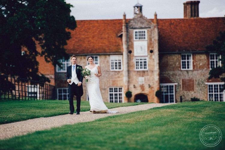 Bride and groom walking in front of Bruisyard Hall, Suffolk. Photography by Lavenham Photographed