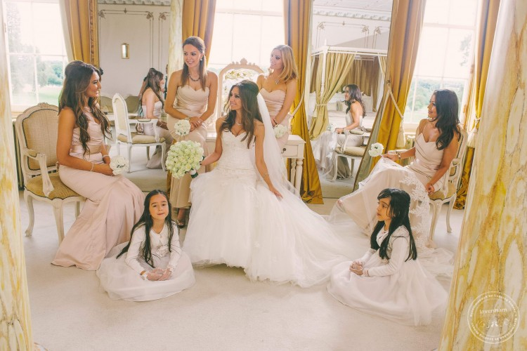 Bride with her bridesmaids photographed sitting in the Rococco suite at Gosfield Hall