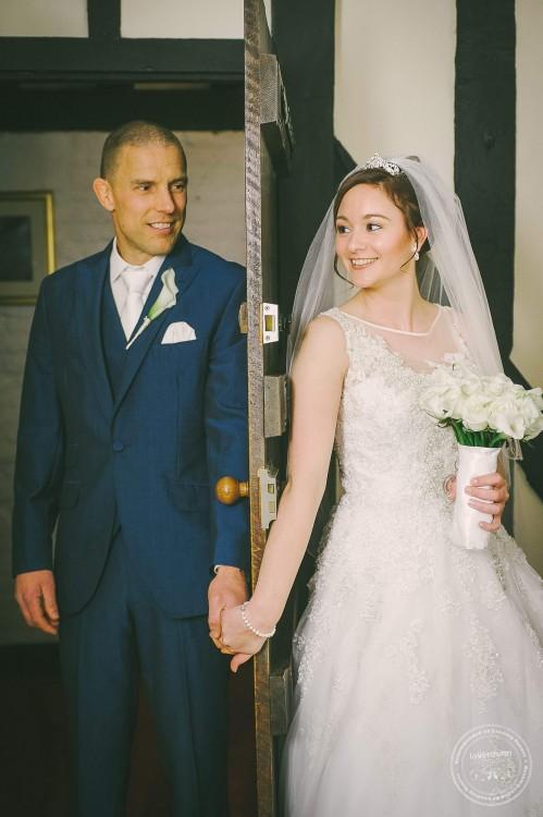 Bride and groom meeting through door before wedding ceremony, Essex Wedding Photographer