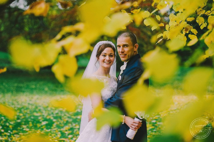 Bride and groom, wedding photography through yellow autumn leaves